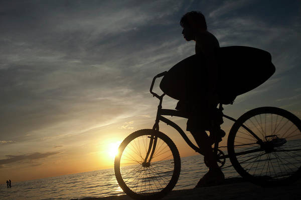 Quintana Roo Photograph - A Surfer Rides A Bicycle In Holbox by Chico Sanchez