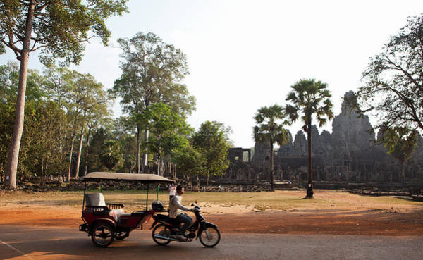 Cambodian Photograph - A Tuk Tuk Drives Past The Bayon In Siem by Dori Moreno