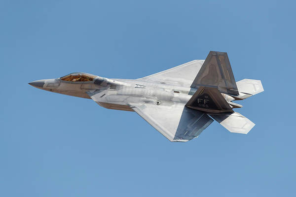 Flying The Flag Wall Art - Photograph - A U.s. Air Force F-22a Takes by Rob Edgcumbe
