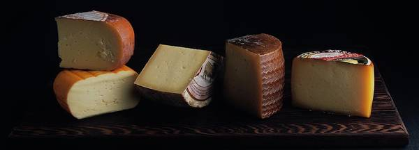 2005 Photograph - A Variety Of Cheese On A Cutting Board by Romulo Yanes