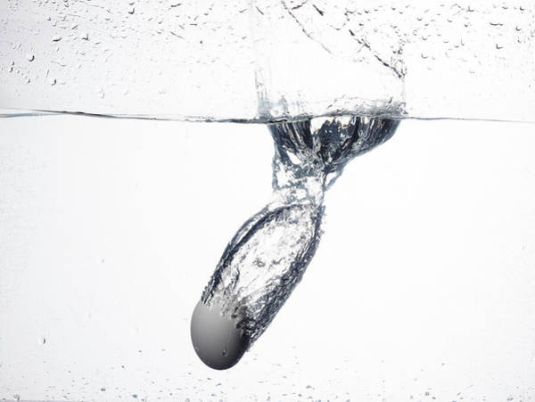 Wall Art - Photograph - A White Birds Egg Dropped Into Water by Rebecca Hale