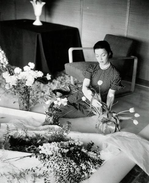 Leaf Photograph - A Woman Arranging Flowers by Horst P. Horst