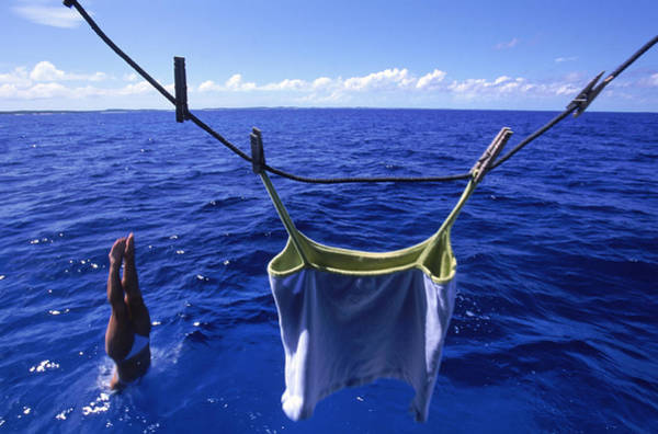 Clothesline Photograph - A Woman Dives Straight Into The Sea by David McLain
