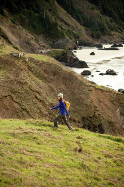 Ecola State Park Photograph - A Woman Hiking Along A Trail Leading by Jordan Siemens