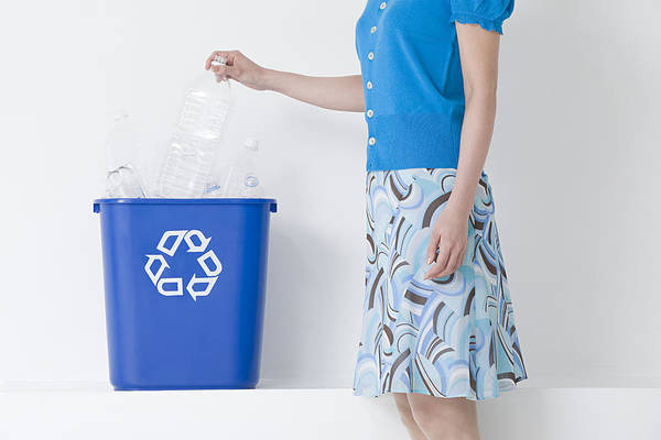 A Woman Putting A Bottle In A Recycling Bin Art Print by Image Source