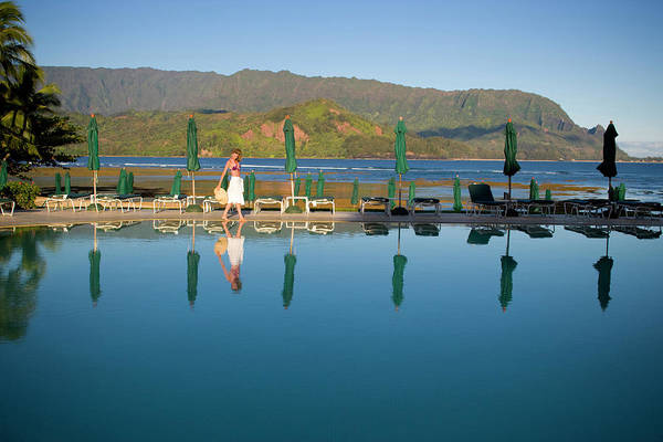 Top Hat Photograph - A Woman Strolls Around A Serene Pool by Jack Affleck