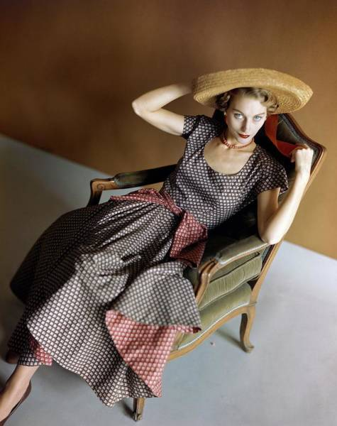 Sun Hat Photograph - A Woman Wearing A Patterned Dress Sitting In An by Horst P. Horst
