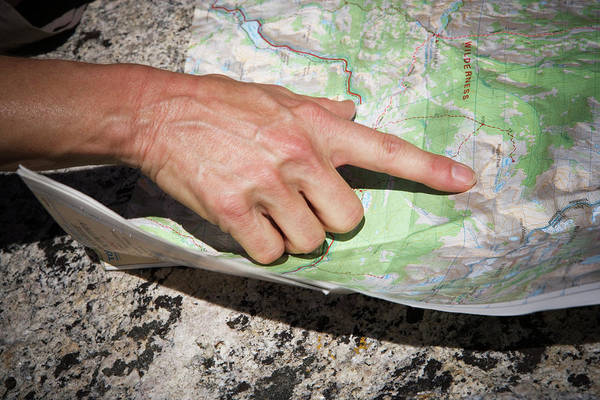 Cartography Photograph - A Womans Hand Pointing To A Location by Ron Koeberer