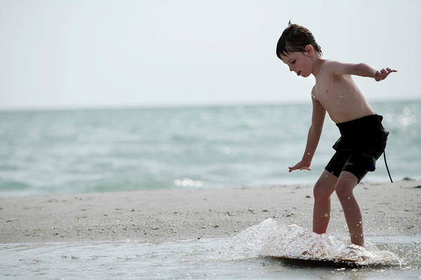 Wetsuit Wall Art - Photograph - A Young Boy In A Wetsuit Surfs by Chris Ross