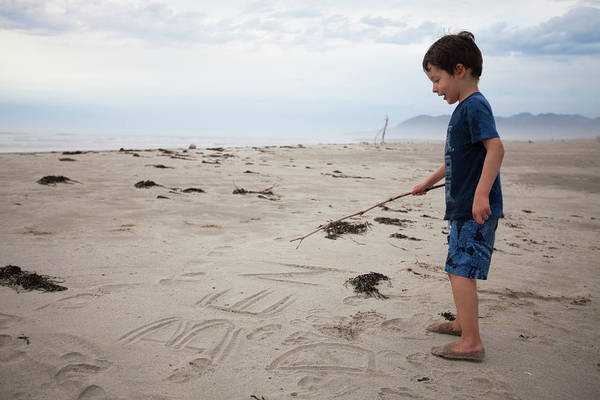 Wall Art - Photograph - A Young Boy Writes His Name In The Sand by Christopher Kimmel