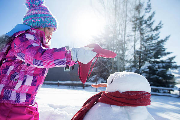 Knit Hat Photograph - A Young Girl Building A Snowman by Mike Schirf