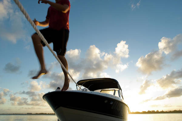 Exuberance Photograph - A Young Man Leaps From Bow Of A Boat by Karsten Moran