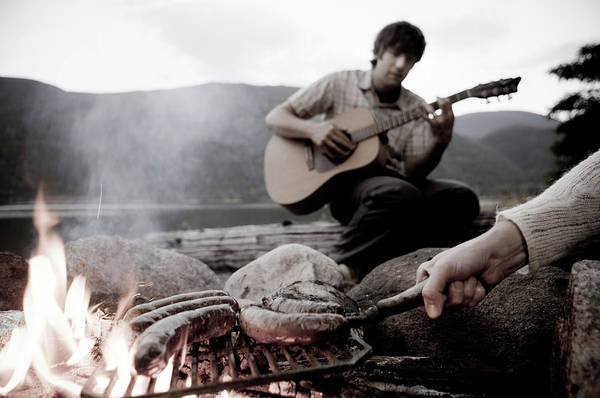 Barbecue Photograph - A Young Man Plays Guitar Next To Meat by Kari Medig