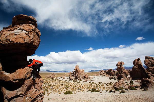 Salar De Atacama Photograph - A Young Man Plays On The Rocks by Michael Hanson