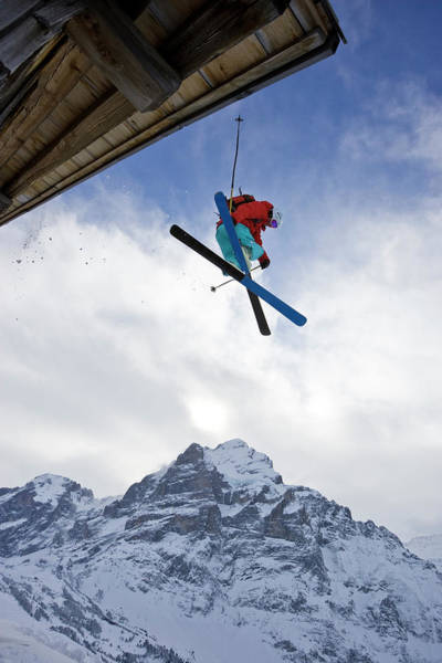 Wall Art - Photograph - A Young Man Skis Off The Roof Of An by Henry Georgi
