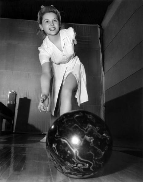 Bowling Alley Photograph - A Young Woman Bowling by Underwood Archives