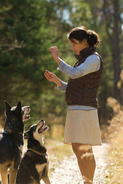 Dog Treat Photograph - A Young Woman Gives Her Dogs Treats by Jeff Diener