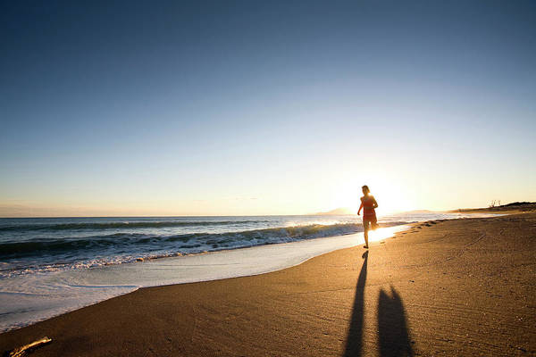 Beach Scene Photograph - A Young Woman Running At Sunset by Damiano Levati