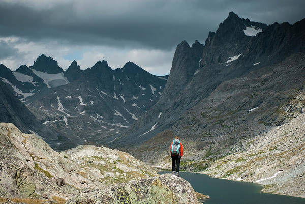 Wind River Range Wall Art - Photograph - A Young Woman Takes In The View While by Jeff Diener
