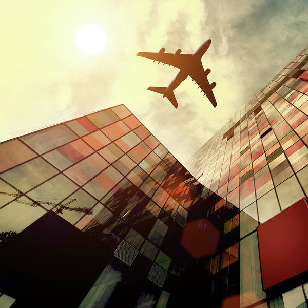 Wing Back Photograph - Airplane Flying Over Building by Teekid
