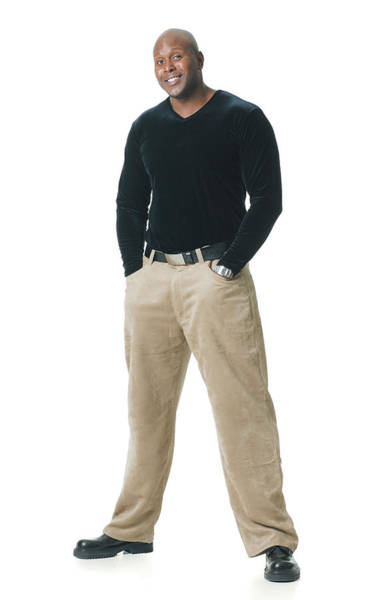 An African American Man In Tan Pants And A Black Shirt Puts His Hands In His Pockets And Smiles Art Print by Photodisc