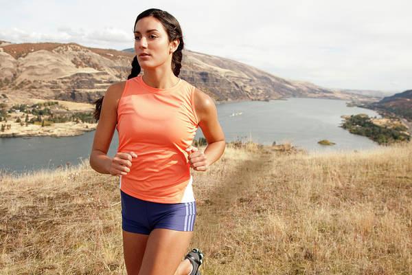 Wall Art - Photograph - An Athletic Female Jogs On A  Dirt by Jordan Siemens