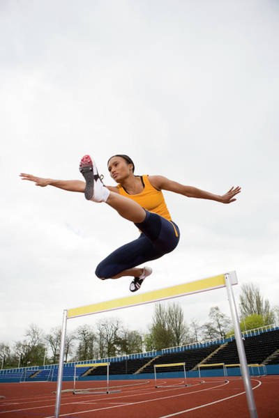 Exertion Wall Art - Photograph - Athlete Clearing A Hurdle by Gustoimages/science Photo Library