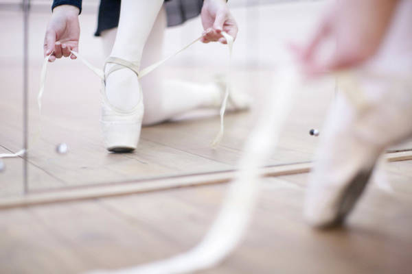 Practice Photograph - Ballerina Putting On Ballet Slippers by Zero Creatives