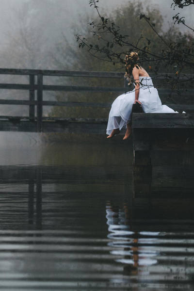 Barefoot Bride In White Wedding Dress Sitting On A Jetty At A La Art Print by Leander Nardin