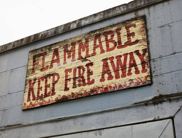 Flammable Wall Art - Photograph - Battered Warning Sign On Building by Nathan Griffith