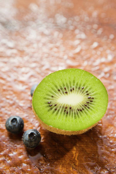 Kiwifruit Photograph - Blueberries And Half A Kiwi Fruit by Foodcollection