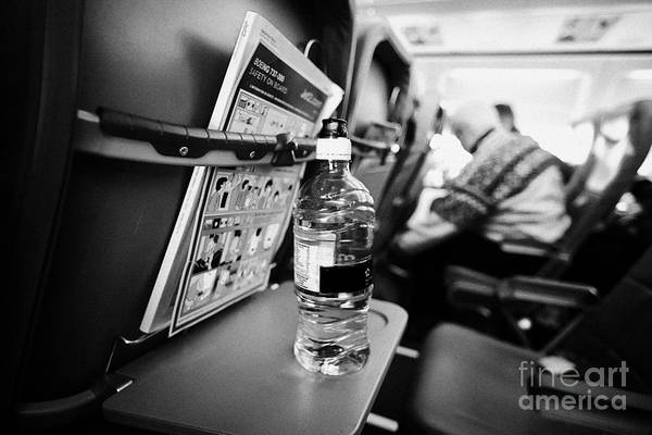 Jet2 Wall Art - Photograph - Bottle Of Water On Tray Table Interior Of Jet2 Aircraft Passenger Cabin In Flight Europe by Joe Fox