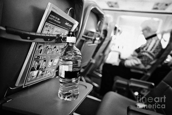 Jet2 Wall Art - Photograph - Bottle Of Water On Tray Table Interior Of Jet2 Aircraft Passenger Cabin In Flight by Joe Fox