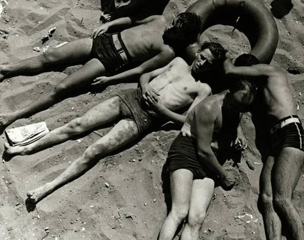 Outdoor Photograph - Boys Lying On The Beach At Coney Island In New by Lusha Nelson