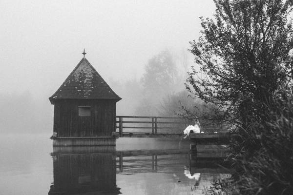 Bride In Foggy Landscape Sitting On A Jetty At A Lake Art Print by Leander Nardin