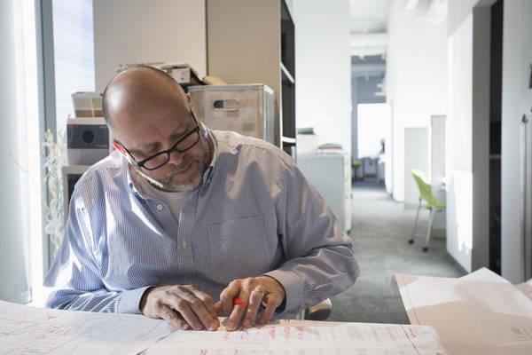 Businessman Sketching Blueprints In Office Art Print by Hill Street Studios