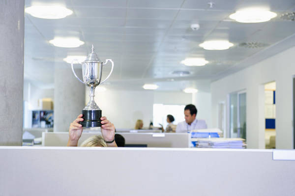 Businesswoman Holding Trophy Over Office Cubicle Art Print by Jacobs Stock Photography Ltd