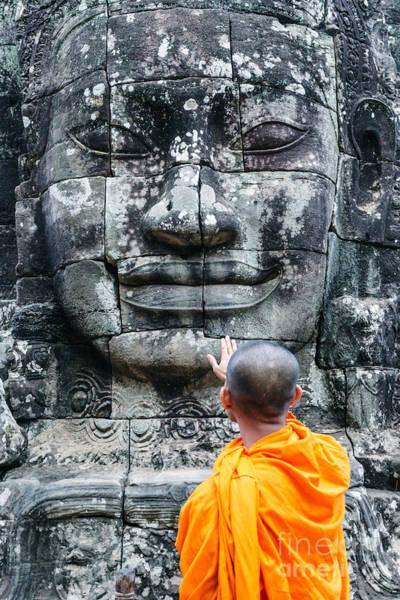 Giant Buddha Photograph - Cambodia - Angkor Wat - Monk Touching Giant Buddha Statue by Matteo Colombo