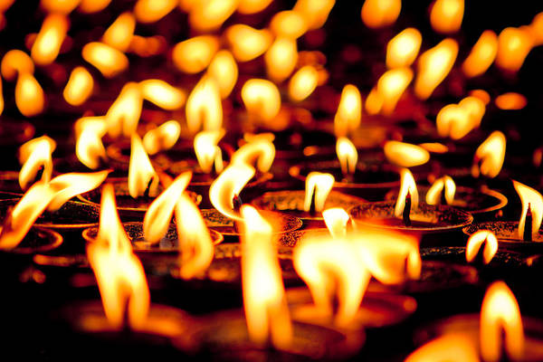 Photograph - candle light in Boudnath stupa by Raimond Klavins