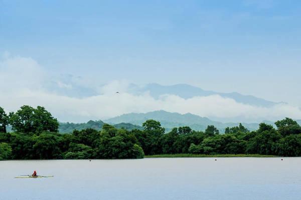 Canoe Photograph - Canoe On A Lake Against Cloud Covered by Amlan Mathur