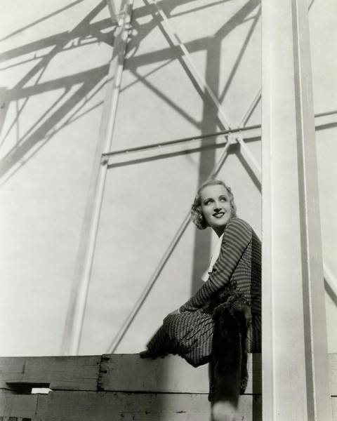 Photograph - Carole Lombard Sitting On A Beam Of A Scaffolded by Cecil Beaton