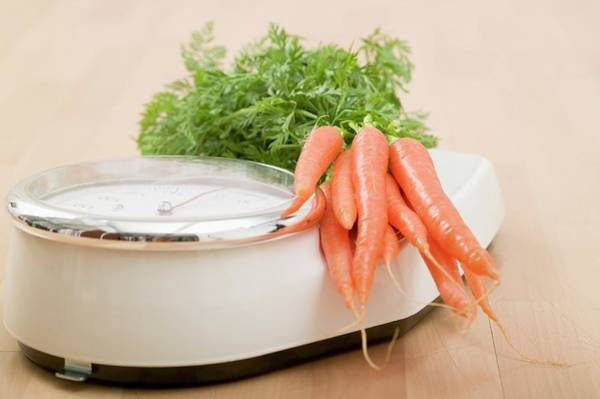 Vegies Photograph - Carrots On Bathroom Scales by Foodcollection