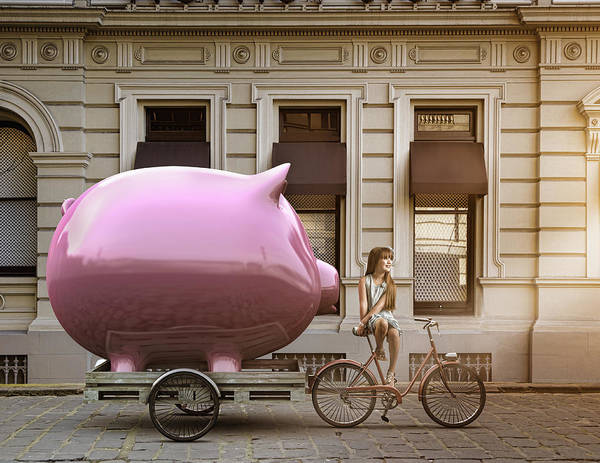 Caucasian Girl Pulling Piggy Bank On Bicycle Cart Art Print by Colin Anderson Productions pty ltd