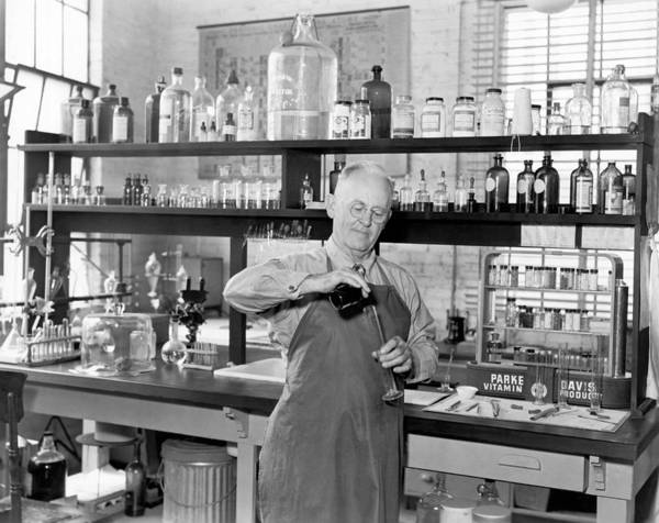 Wall Art - Photograph - Chemist Working In A  Lab by Underwood Archives