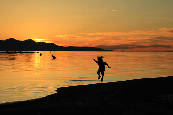 Photograph - Child Playing While The Sun Sets. by Johnny Adolphson