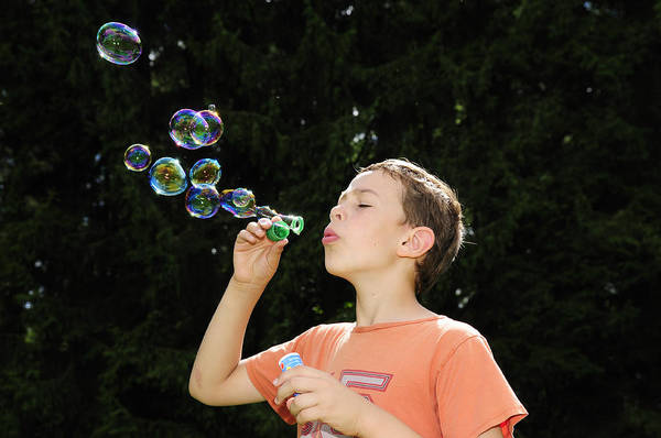 Photograph - Child Playing With Bubbles by Matthias Hauser
