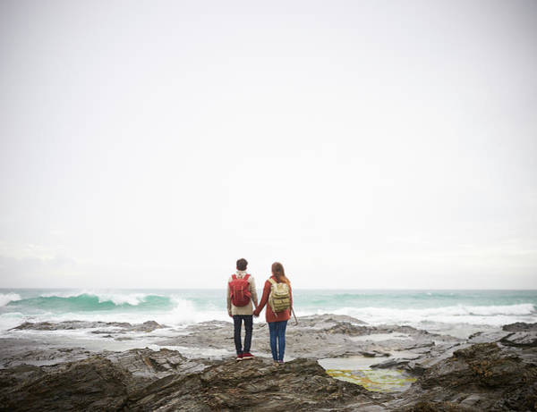 Heterosexual Couple Photograph - Couple Holding Hands And Looking Out To by Dougal Waters