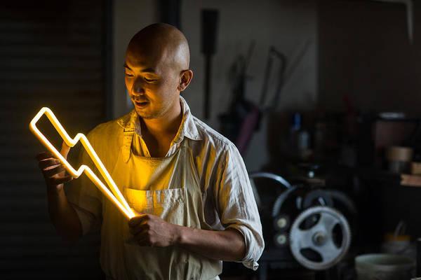 Craftsmen Holding A Lightning Bolt Shaped Neon Light Art Print by Trevor Williams