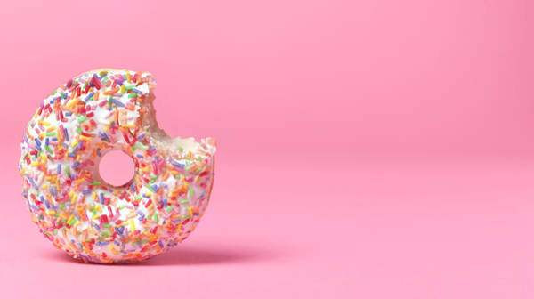 Sprinkles Photograph - Doughnut On Pink With Bite Out by Peter Dazeley