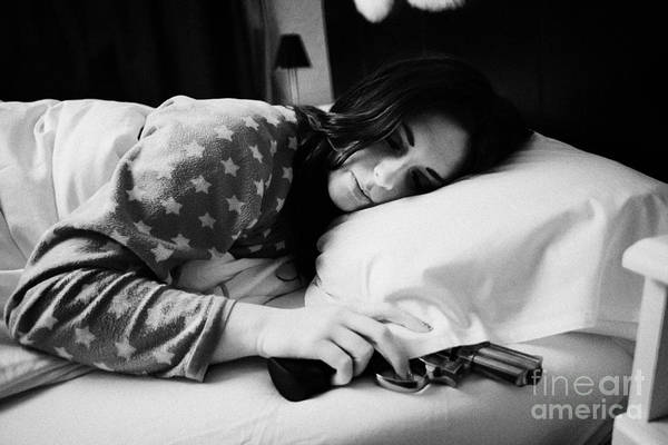 Wall Art - Photograph - Early Twenties Woman With Hand On Handgun Under Pillow At Night In Bed In A Bedroom by Joe Fox